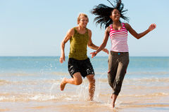 Sport couple jogging on the beach. Young sport couple - Caucasian man and African-American woman - jogging on the beach in a playful mode Royalty Free Stock Photo