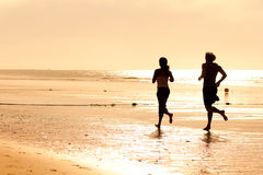 Sport couple jogging on the beach. Young sport couple - jogging on the beach in sunset Royalty Free Stock Photos