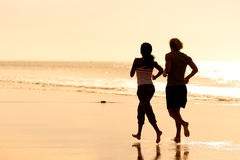 Sport couple jogging on the beach. Young sport couple - jogging on the beach in sunset Royalty Free Stock Photography