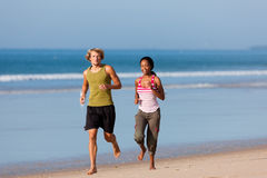 Sport couple jogging on the beach. Young sport couple - Caucasian man and African-American woman - jogging on the beach Stock Image