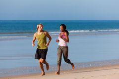 Sport couple jogging on the beach. Young sport couple - Caucasian man and African-American woman - jogging on the beach stock images