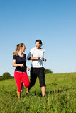 Sport couple jogging outdoors in summer. Young fitness couple doing sport outdoors, jogging on a green summer meadow in the grass under a clear blue sky Royalty Free Stock Photo