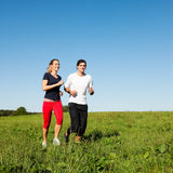 Sport couple jogging outdoors in summer. Young fitness couple doing sport outdoors, jogging on a green summer meadow in the grass under a clear blue sky Stock Photos