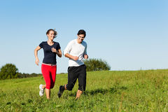 Sport couple jogging outdoors in summer. Young fitness couple doing sport outdoors, jogging on a green summer meadow in the grass under a clear blue sky Stock Photo