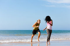 Sport couple playing  on the beach. Young sport couple - Caucasian man and African-American woman - jogging on the beach in a playful mode Royalty Free Stock Photography