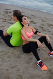 Sport couple resting after jogging outdoors sitting on sand. Fitness couple resting after workout sitting on the beach, exhauster after run charming women taking Royalty Free Stock Photography