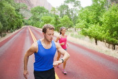 Sport - couple running exercising using watch Stock Photo