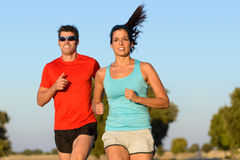 Sport couple running. Fitness couple running in country road. Cheerful runners training outdoors on summer for sport and healthy lifestyle Royalty Free Stock Image