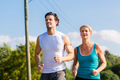 Sport couple running and jogging on rural street Stock Photo