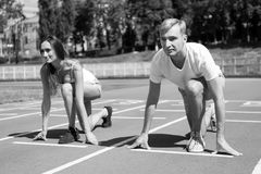 Sport couple start competition running at arena track. Sunny summer outdoor stock photo