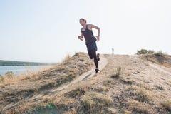 Sport courant Sprinter de turbine d'homme extérieur en nature scénique Traînée masculine musculaire convenable de formation d'ath Images libres de droits
