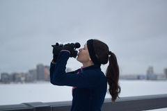 Sport cute woman drinks water during jogging outside at cloudy winter day Stock Photo