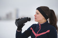 Sport cute woman drinks water during jogging outside at snow winter day Royalty Free Stock Photos