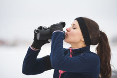 Sport cute woman drinks water during jogging outside at snow winter outdoor royalty free stock photos