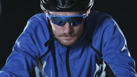 Sport cyclist riding bicycle in goggles and helmet stock footage