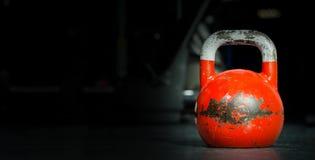 Sport de cloche de bouilloire, vieux poids utilisé lourd de kettlebell de couleur sur le plancher de gymnase prêt pour la séance  photographie stock