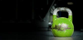 Sport de cloche de bouilloire, vieux poids utilisé lourd de kettlebell de couleur sur le plancher de gymnase prêt pour la séance  images libres de droits