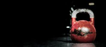 Sport de cloche de bouilloire, vieux poids utilisé lourd de kettlebell de couleur sur le plancher de gymnase prêt pour la séance  photos libres de droits
