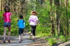 Sport de famille, mère active heureuse et enfants pulsant dehors Image libre de droits