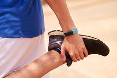 Sport del giovane che allungano facendo uso del contatore di operazioni successive di Fitwatch Immagini Stock Libere da Diritti