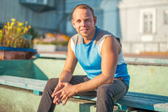Sport dell'uomo attraente che si siede sul banco e sui resti nello stadio Immagini Stock Libere da Diritti
