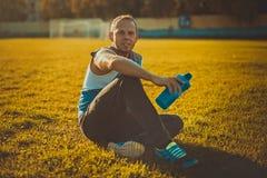 Sport dell'uomo attraente che si siede sull'erba e Immagini Stock Libere da Diritti