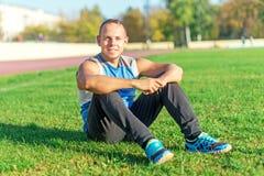 Sport dell'uomo attraente che si siede sull'erba e Immagini Stock