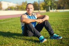 Sport dell'uomo attraente che si siede sull'erba e sui resti nello stadio Immagine Stock