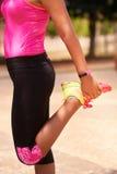 Sport della donna che allungano facendo uso del contatore di operazioni successive di Fitwatch Fotografia Stock Libera da Diritti