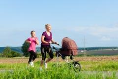 Sport della famiglia - pareggiando con il passeggiatore di bambino immagine stock