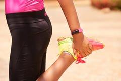 Sport della giovane donna che allungano facendo uso del contatore di operazioni successive di Fitwatch Fotografia Stock Libera da Diritti