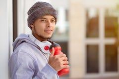Sport, der das Trinkwasser des jungen lateinischen Mannes schaut herauf denkenden Läufer copyspace Kopienraum ausbildet stockfotos