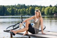 Sport, der die junge Frau sitzt durch See radfährt stockfotos