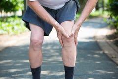 Sport, der Knieverletzung im männlichen Seitentrieb laufen lässt Stockfotografie