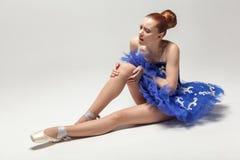 Sport, der Knieverletzung im männlichen Seitentrieb laufen lässt Ballerina mit Brötchen sammelte das Haar, das blaues Kleid trägt stockfoto