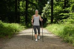 Sport di camminata nordico di ricreazione della donna fotografia stock