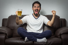 Sport di sorveglianza dell'uomo entusiasta sulla TV e sul gruppo di sostegno ad uff Immagini Stock