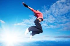 Sport die springende Frau und fliegen Sie über Himmel und Sonne Stockfotografie