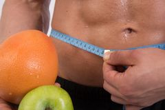 Sport and diet. Attractive man with muscular body. Athletic guy and fruits. Man measuring tape body. Healthy eating Royalty Free Stock Images