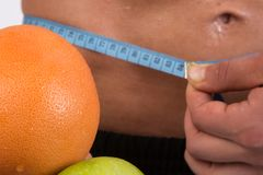 Sport and diet. Attractive man with muscular body. Athletic guy and fruits. Man measuring tape body. Healthy eating Stock Photography