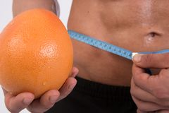 Sport and diet. Attractive man with muscular body. Athletic guy and fruits. Man measuring tape body. Healthy eating Royalty Free Stock Photos