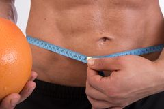 Sport and diet. Attractive man with muscular body. Athletic guy and fruits. Man measuring tape body. Healthy eating stock images