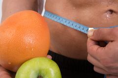 Sport and diet. Attractive man with muscular body. Athletic guy and fruits. Man measuring tape body. Healthy eating Royalty Free Stock Photo