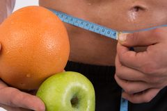 Sport and diet. Attractive man with muscular body. Athletic guy and fruits. Man measuring tape body. Healthy eating Stock Photos