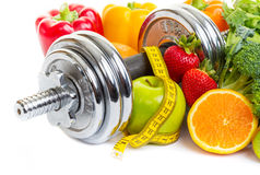 Sport Diet. Chrome dumbbells surrounded with healthy fruits and vegetables on a white background Stock Images
