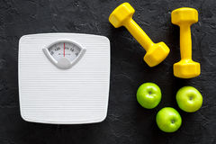 Sport and diet for losing weight. Bathroom scale, apple and dumbbell on black background top view Royalty Free Stock Photo