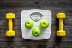 Sport and diet for losing weight. Bathroom scale, apple and dumbbell on wooden background top view Royalty Free Stock Image