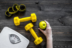 Sport and diet for losing weight. Bathroom scale, apple and dumbbell on wooden background top view copyspace. Sport and diet for losing weight. Bathroom scale Stock Images