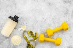Sport diet protein nutrition and fitness equipment on stone background top view mock up. Sport diet protein nutrition and fitness equipment on gray stone Royalty Free Stock Images