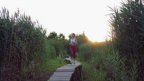 Sport draußen, aktives Athletenmädchen mit schöner Zahl Läufe auf Holzbrücke in der Natur unter Gras bei Sonnenuntergang stock video footage